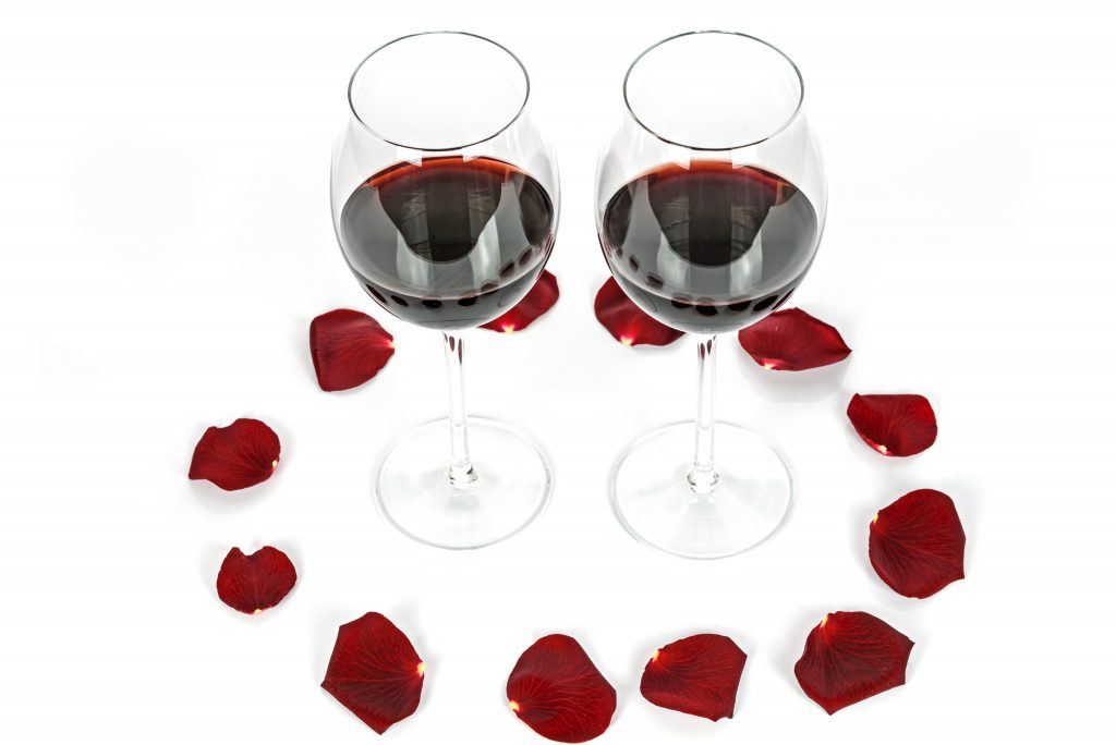 Two glasses of wine surrounded by red rose petals